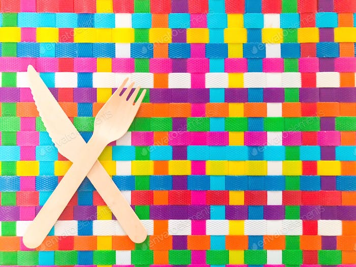 Knife and fork on bright colorful weaved placemat background with space for copy