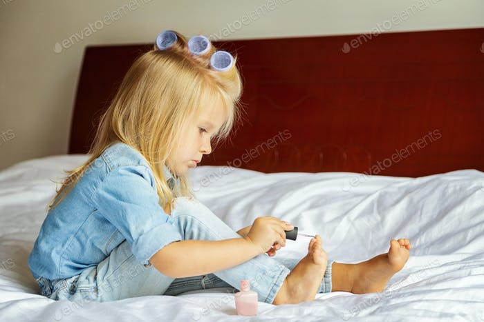 ⭐️⭐️⭐️ Nominated ⭐️⭐️⭐️ cute little girl with blonde hair in hair curlers sitting at home on the bed