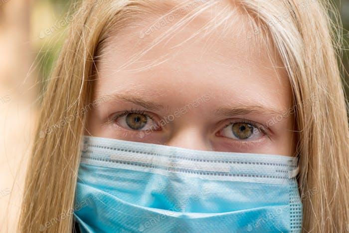 Ein Mädchen mit Einweg-Gesichtsmaske. Obligatorisch obligatorische Masken. Coronavirus COVID-19-Konzept