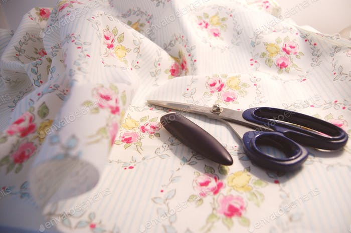 Fabric shears and tailor's chalk lying on floral fabric