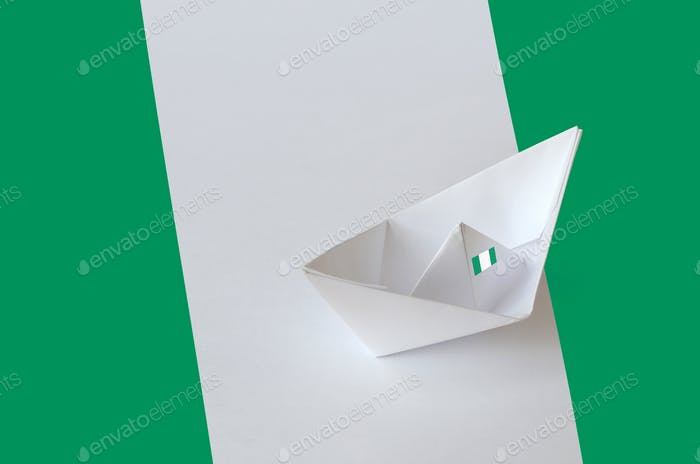 Nigeria flag depicted on paper origami ship closeup. Oriental handmade arts concept