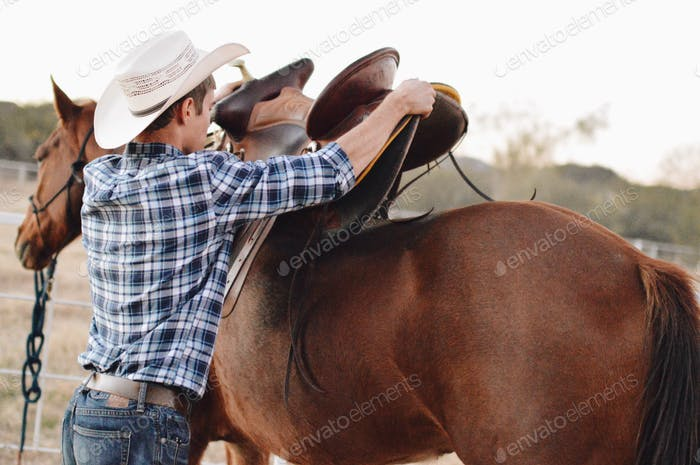 A man getting ready to go horse back riding.