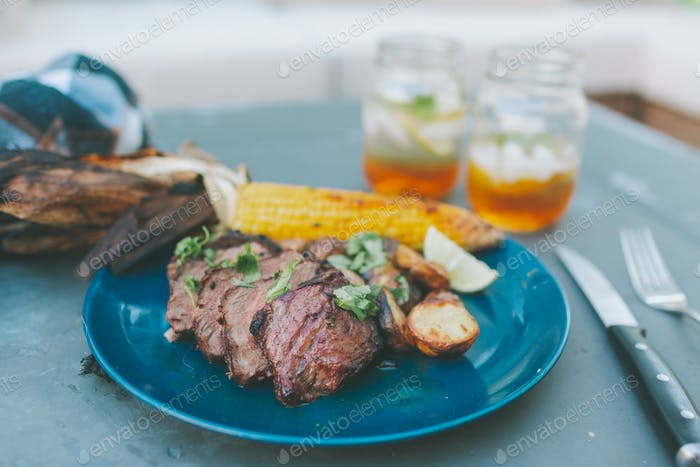 A plate of barbecued steak and corn.