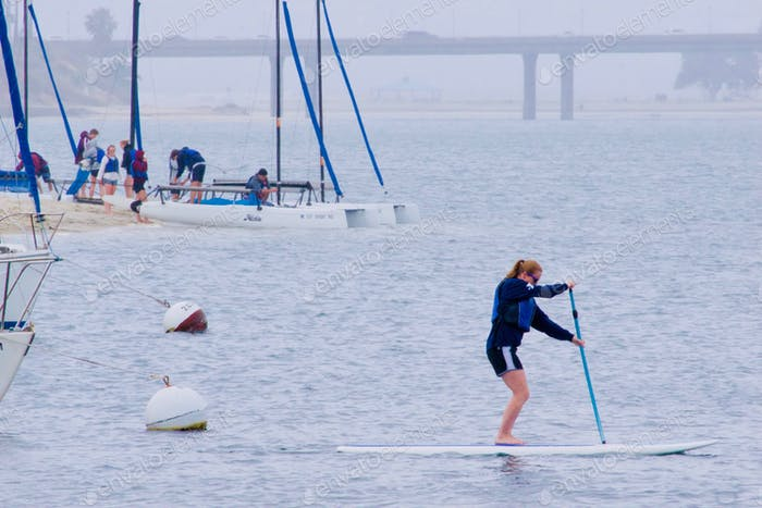 A woman is exercising on her standup paddleboard in the early morning fog