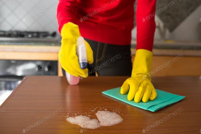 Chica con guantes amarillos y detergente