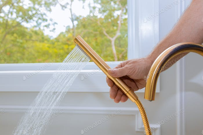 Shower head with water stream in domestic bathroom