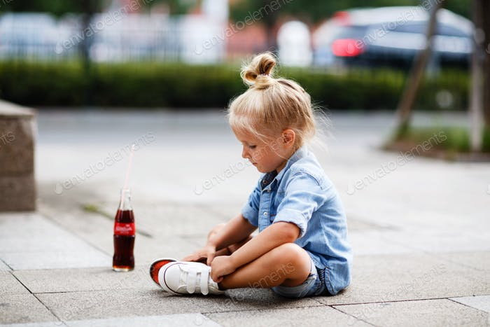 ⭐️⭐️⭐️ Nominated ⭐️⭐️⭐️     Stylish little girl sitting on the road outdoor with bottle of Coca-Cola