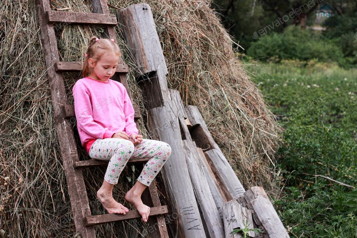 girl in a pink sweater sits by a haystack on a wooden ladder,