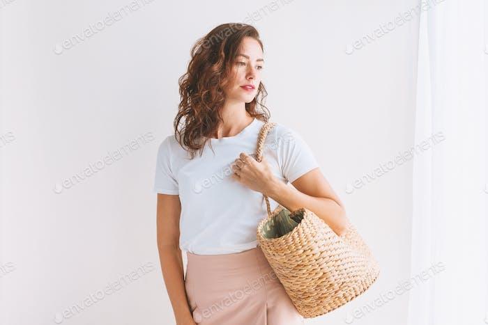 Fashionable stylish woman holding straw rattan bag