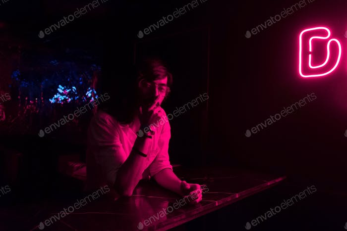 A Drunk Young Adult looking straight while sitting inside a Night Club under a Neon Disco Light Sign