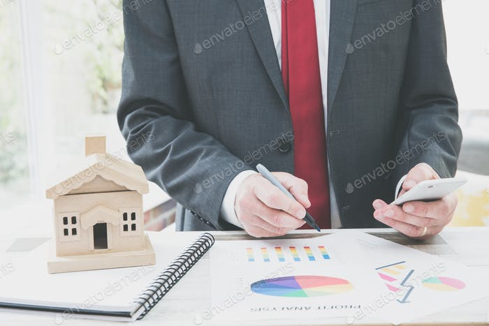 Ein Geschäftsmann Immobilienmakler, ein Immobilienentwickler, der an seinem Schreibtisch arbeitet und Wohnungsdaten analysiert