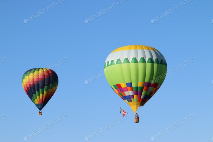 Colorful hot air balloons against blue sky.
