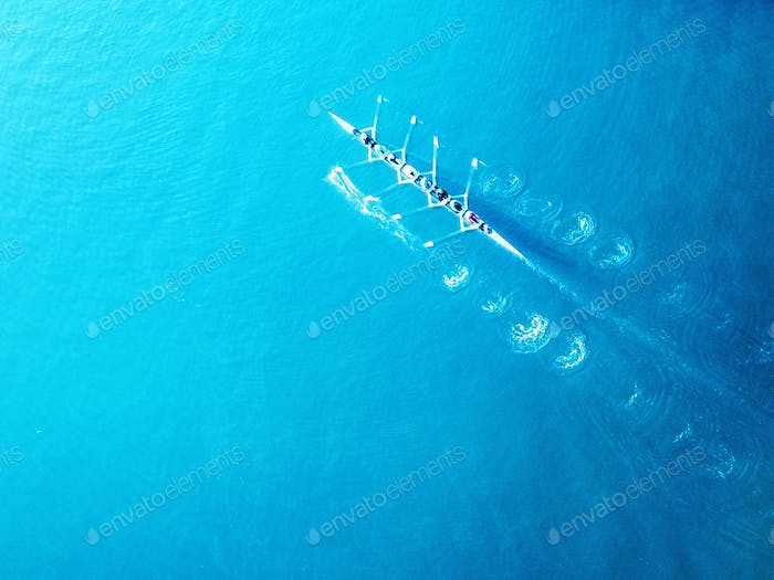 An aerial shot of a rowing boat surrounded by turquoise waters. Bright and bold.