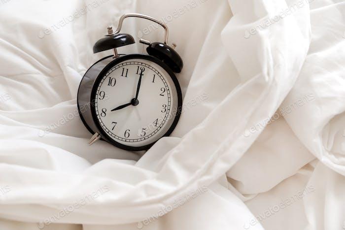 Classic alarm clock in bed