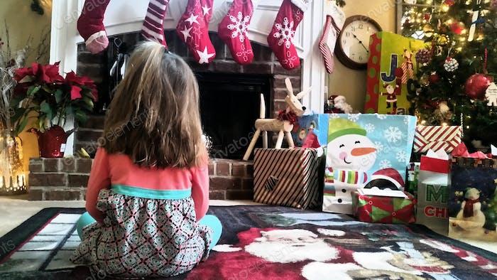Kleines Mädchen wartet geduldig darauf, dass der Weihnachtsmann ankommt.