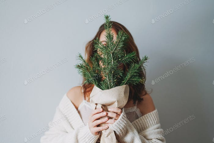 Attractive friendly smiling brunette woman with winter fir brunches near face at home cozy vibes