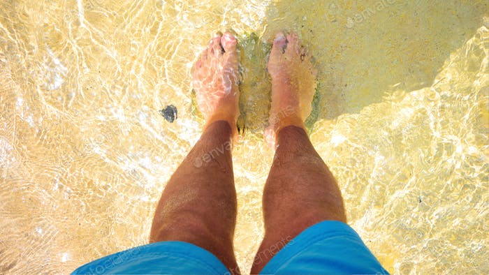 Man male feet legs standing water beach