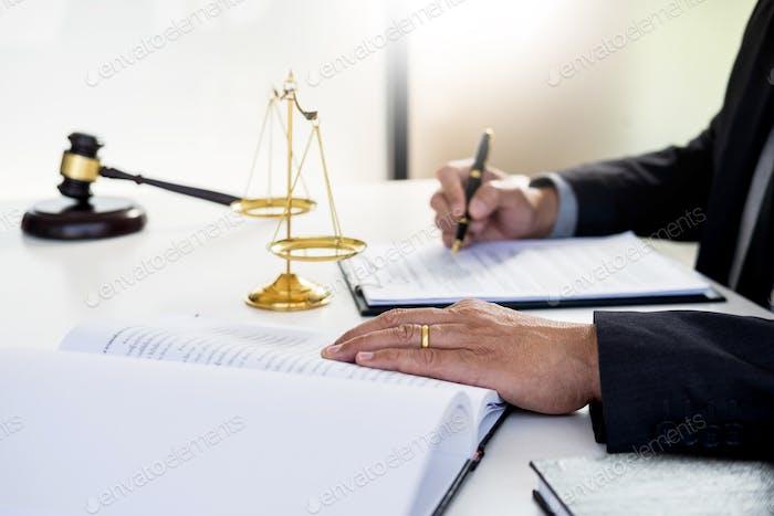 juez abogado lectura y escribe el documento en la corte en su escritorio.