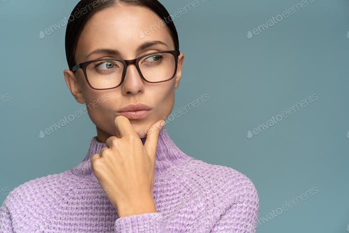 Serious business woman in sweater wear glasses puts her chin, thinking, looking at copy space.