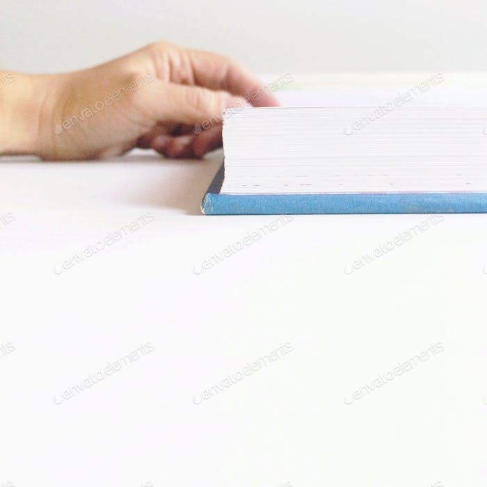 Hand resting on an open hardback book page on a white background.