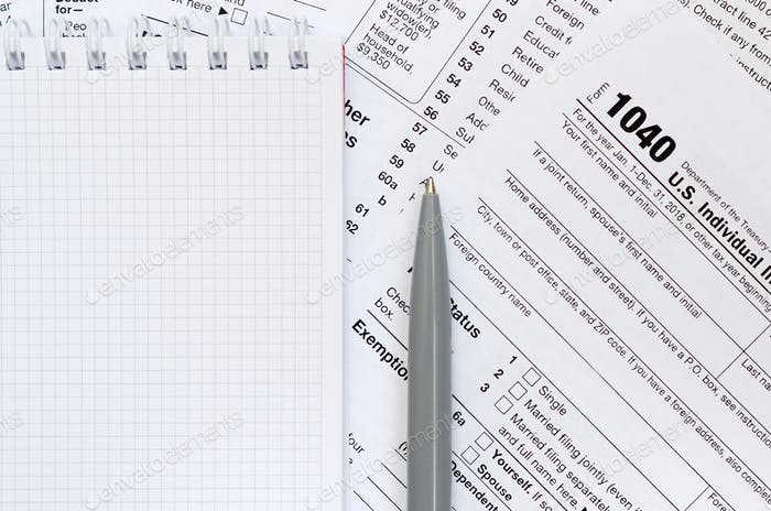 The pen and notebook is lies on the tax form 1040 U