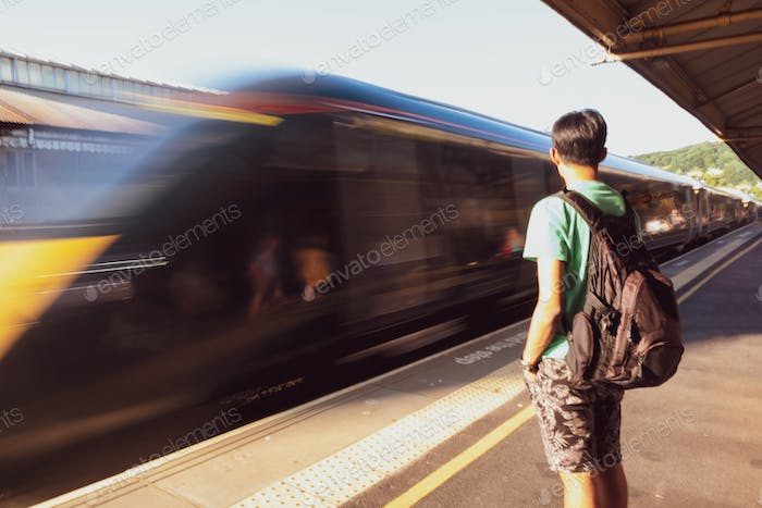 A traveller waiting for a train at the station. Speeding train. Moving train. People, traveling , tr