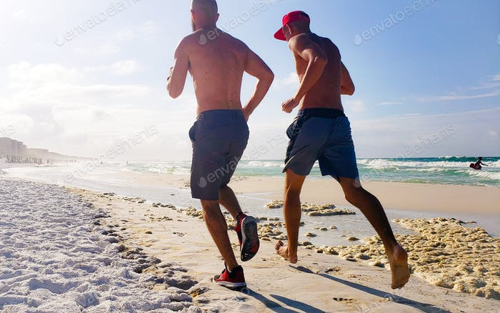 Two millenials running together seaside having fun getting fit for their girlfriends who are right