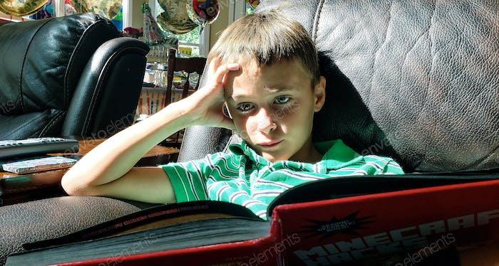Kleiner Junge liest ein Buch, sobald seine 2 Stunden Internet pro Tag aufgebraucht sind... er ist nicht glücklich...