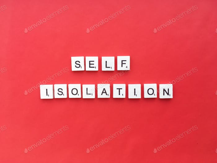 Self isolation scrabble letters word on a red background