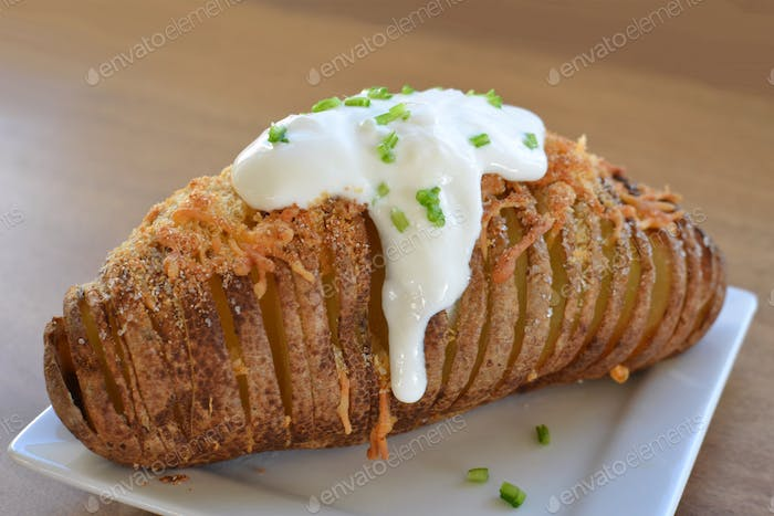 Hasselback baked potatoes or Potato à la Hasselbacken topped with cheese, sour cream and chives.