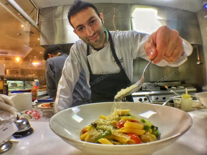 Chef drizzles parmesan cheese generously on gluten free  chicken with vegetables penne pasta
