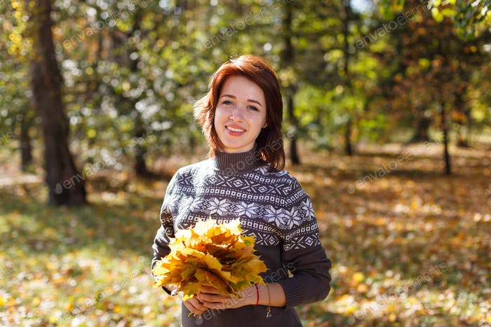 Beautiful young woman with light brown hair in sweater on background of foliage
