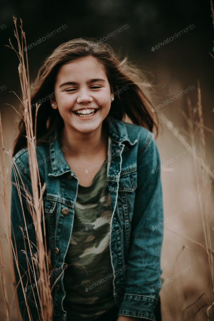 Girl on a windy fall day laughing, preteen