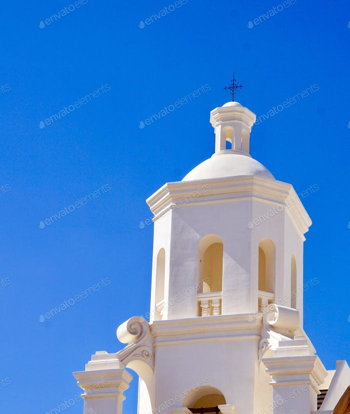 Top of a beautiful white bell tower on a church which is an old Spanish mission and a beautiful blue