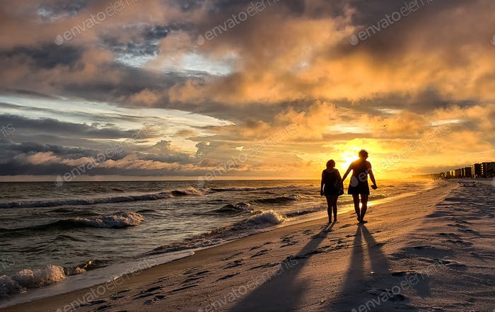 Two women walking down the beach could be a couple but dressed in a cloak of black while walking