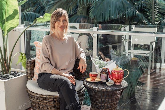 Beautiful mature woman drinking tea or coffee on the tropical balcony