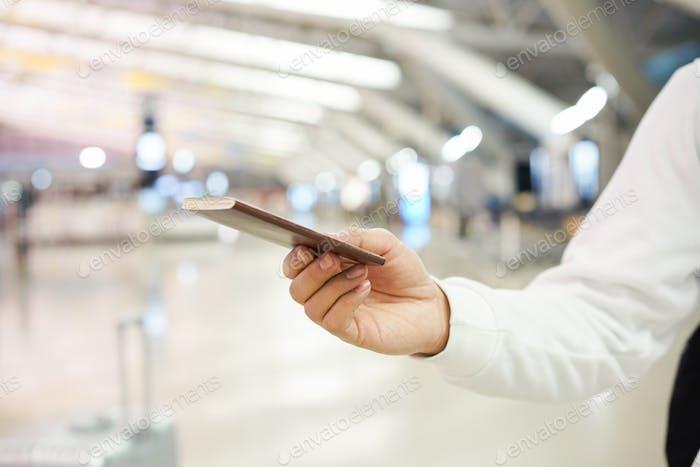 cerrar el viajero hombre de la mano con pasaporte y enviado al personal de inmigración para el control y verificación