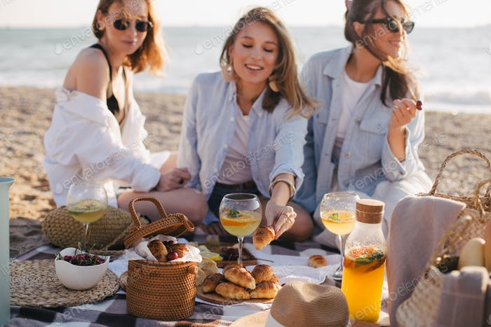 Three young women female friends having picnic on a beach drinking cocktails and eating croissants