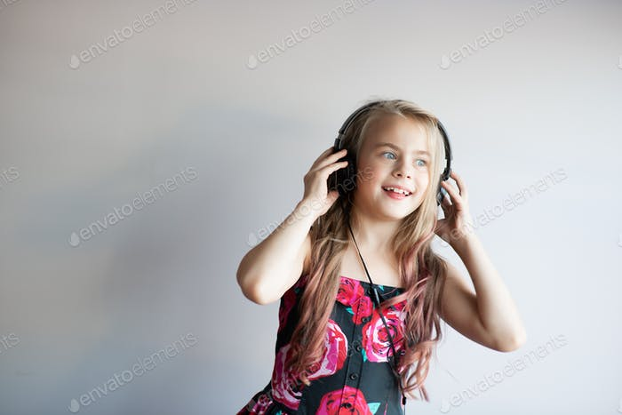 Beautiful elementary age little girl with curly hair listening to music with headphones and dancing