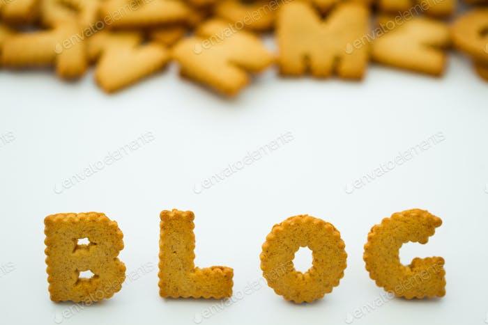 La palabra blog deletreado con galletas en forma de alfabeto sobre un fondo blanco.