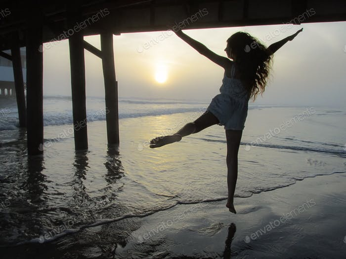 Young woman millennial air jumping for joy under ocean pier along shoreline & silhouetted at sunrise