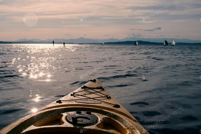 Point of view from a sea kayak with paddle boarder