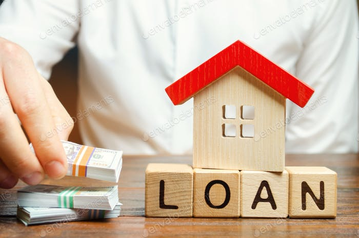 Wooden blocks with the word Loan, house and money in the hands of a businessman