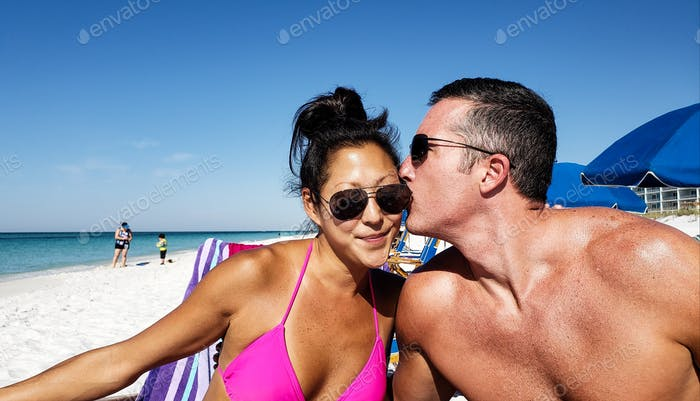 Generation X couple on the beach with husband either whispering in her ear or biting her ear but she