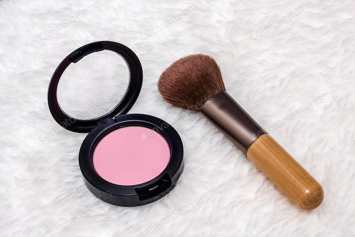 Pink blush and powder brush on the white background