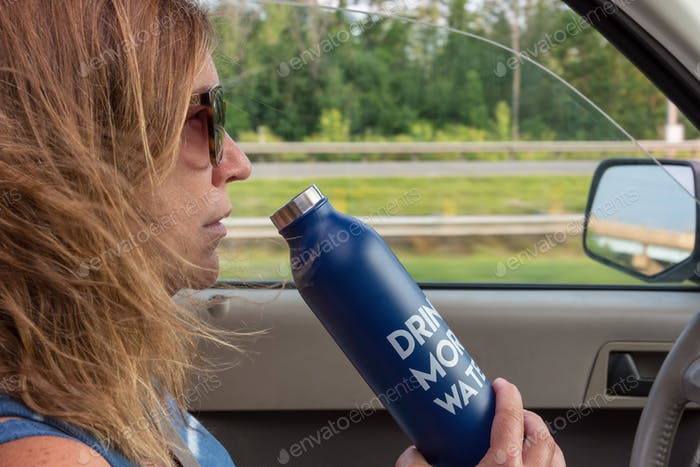 Woman driving a car drinking from an aluminum water bottle