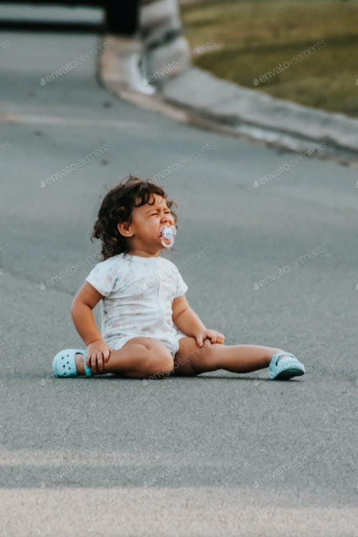 niño llorando, berrinche mientras juega afuera en la calle, emoción, momento sincero de la vida real