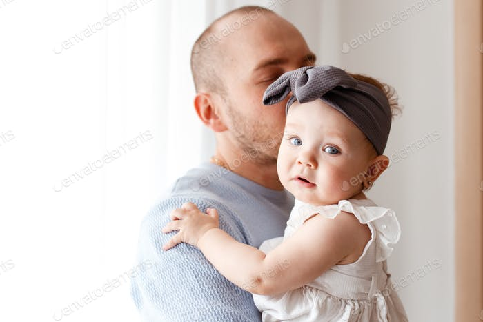 dad and daughter, dad in a blue sweater hugs, kisses and soothes his baby daughter in a white dress