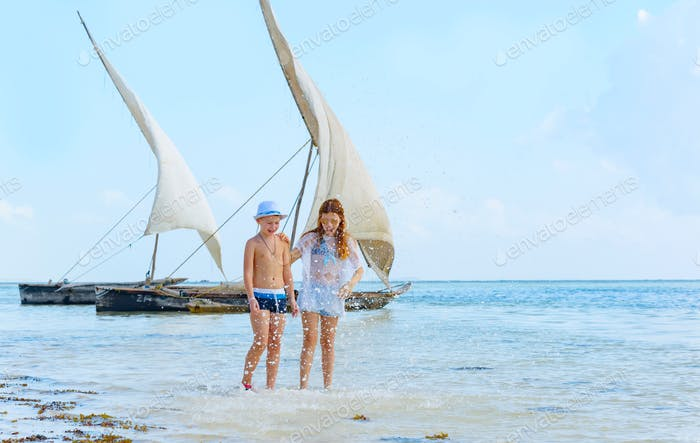 boy and girl having fun in the background of traditional African solid wood boats under sail on