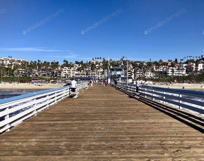 People walking along pier on beautiful day